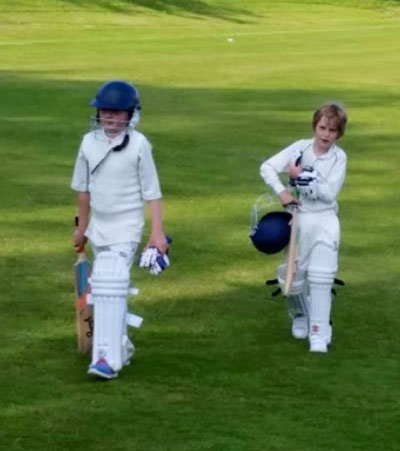 Lily and Henry walking off the field after batting against Weymouth